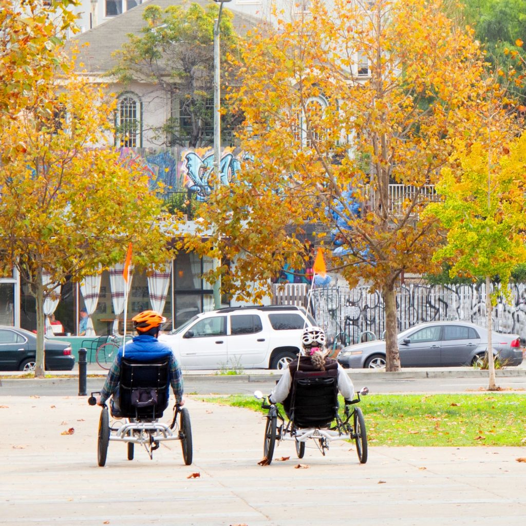 a man and a woman ride in recumbent seats on low tricycles