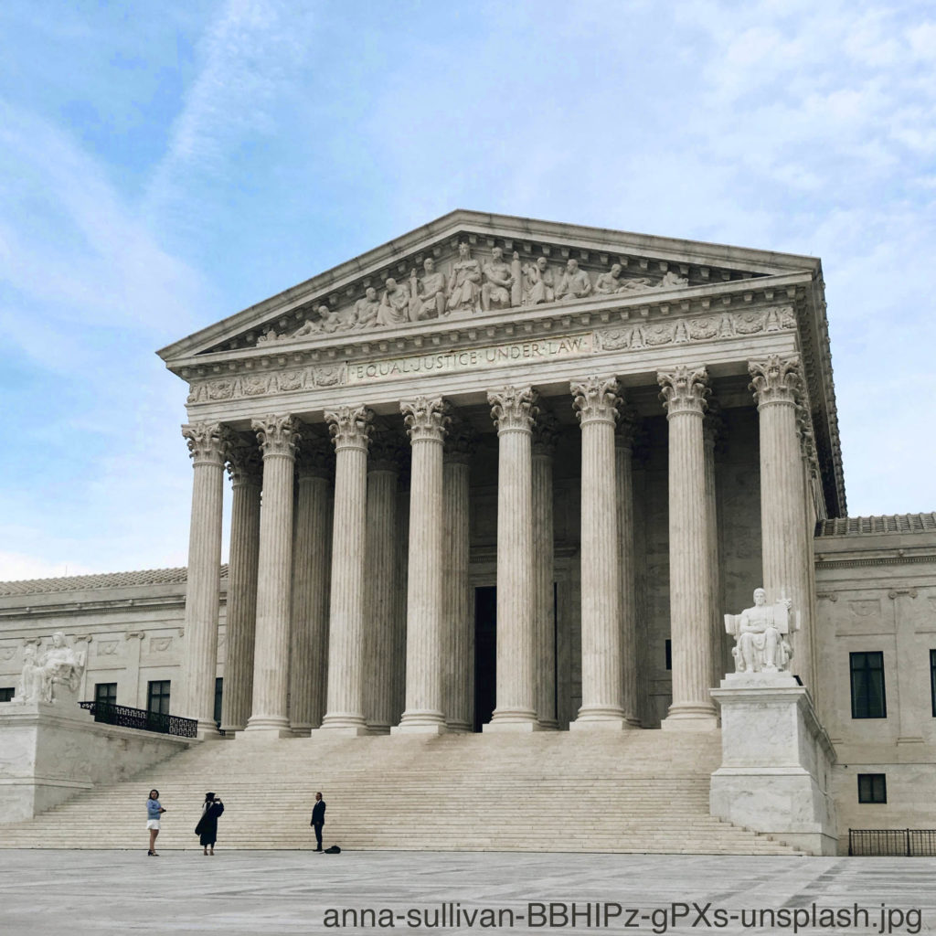 A photographer snaps a photo of a person at the foot of the grand staircase of the Supreme Court building in Washington DC