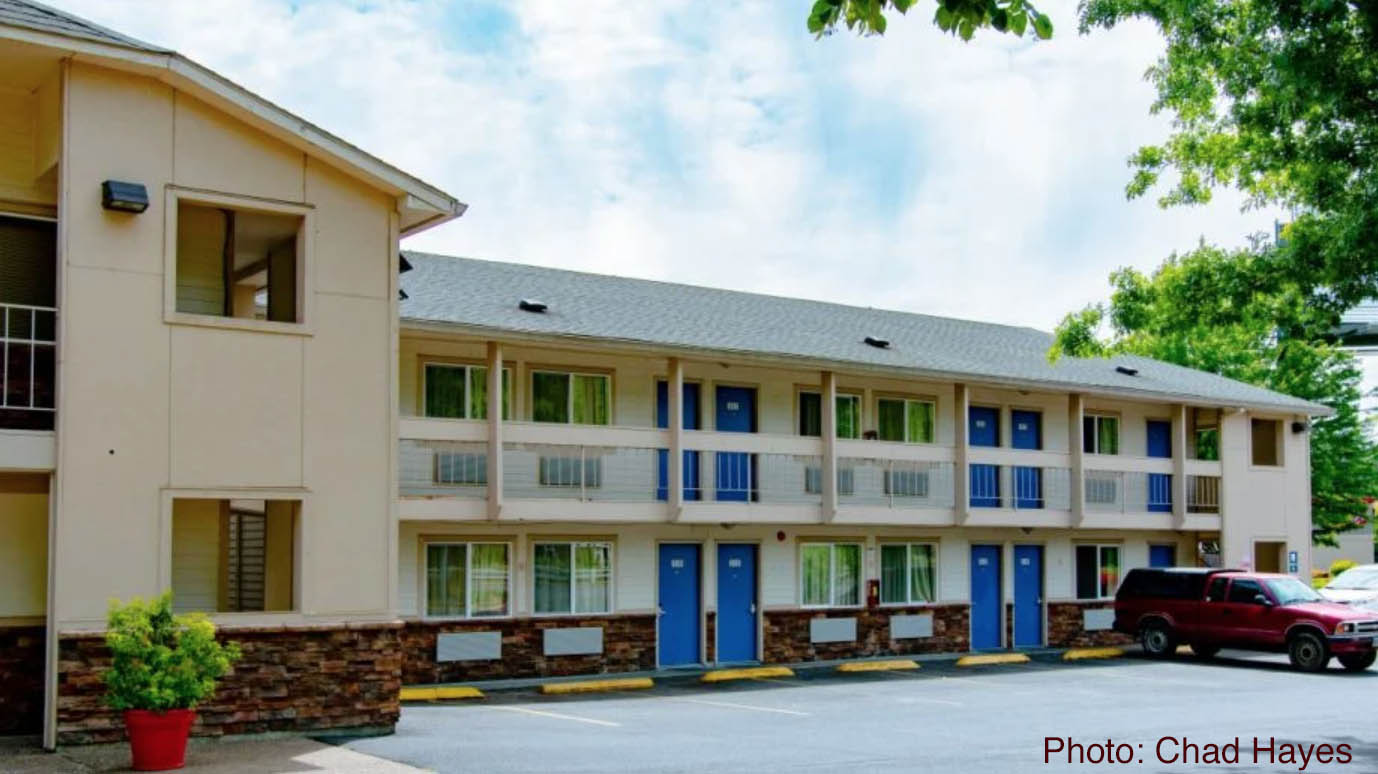 A three-story motel with five blue entry doors on each floor faces a parking lot in which a single red truck is parked