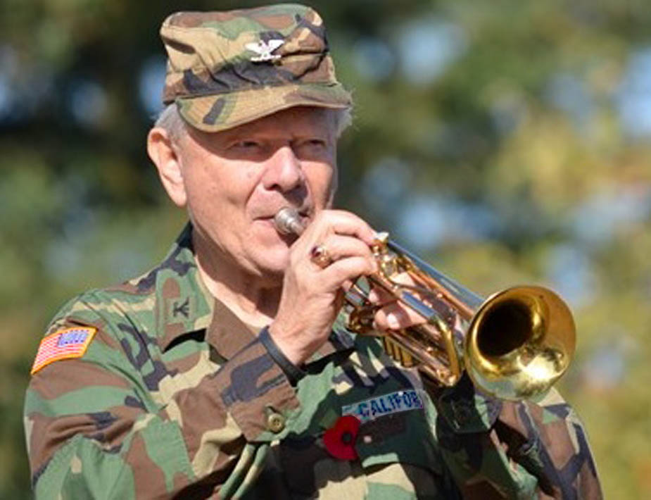 Bird colonel in camo and cap playing trumpet
