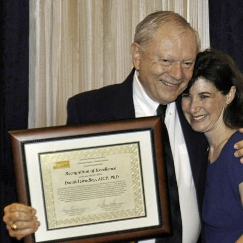 Elderly man places arm on shoulder of younger woman younger woman as he holds framed certificate in other hand so we can see it