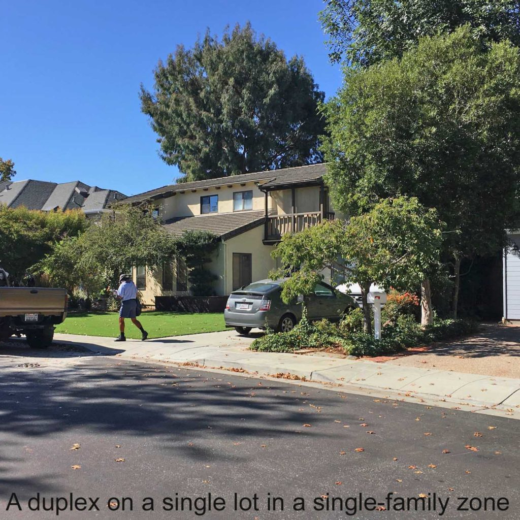 a mail carrier walks by two-story two-family house