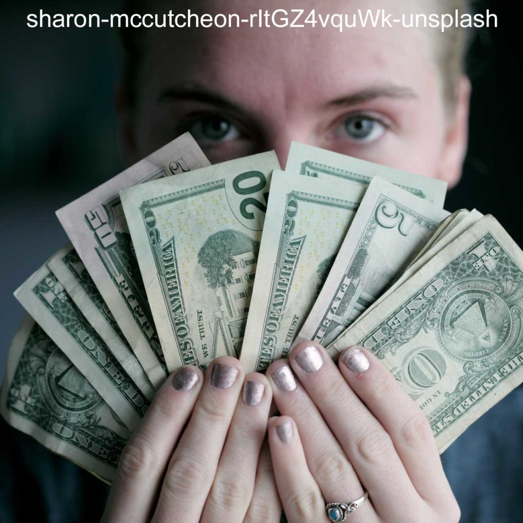 Woman with painted nails shows a fan of various US currency, from one dollar to fifty