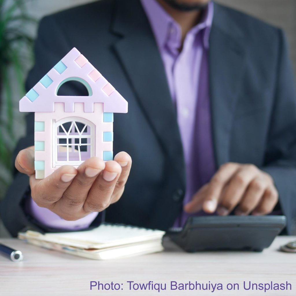 A man holds a model of a tiny house in one hand and taps a calculator with the other