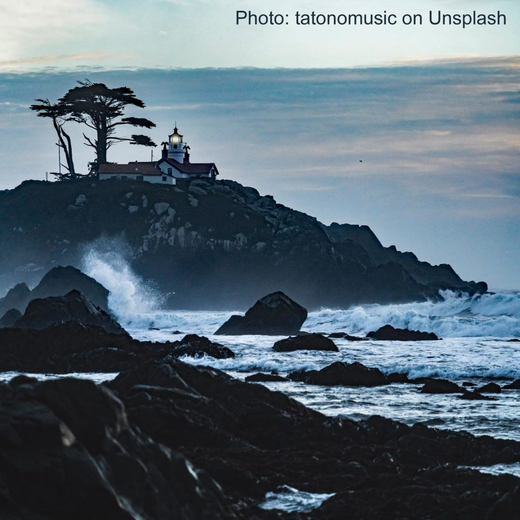 A lighthouse on top of a rocky crag with waves pounding below
