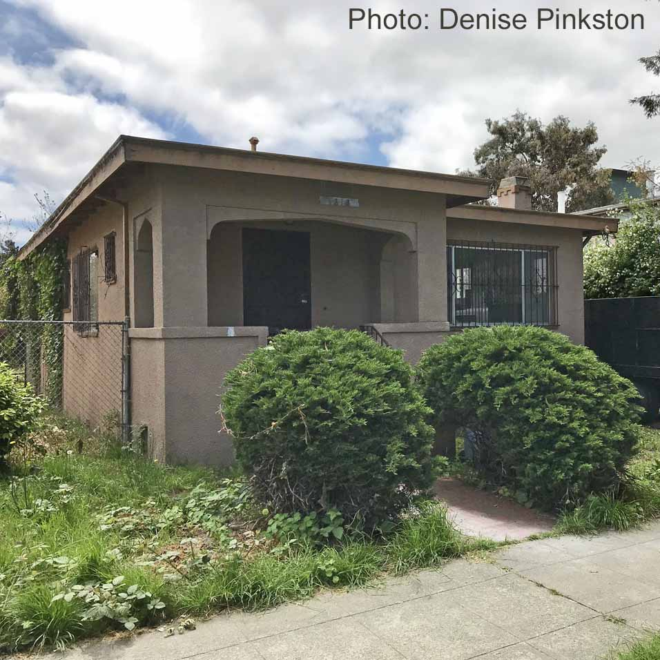 A brown stucco house, quite small, sits vacant. Two round, green bushes flank the short entry walk.